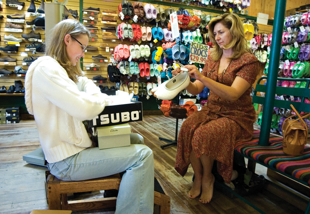 Local resident Suzie Hawkins, right, gets some help from Steamboat Shoe Market employee Andrea Erickson, left while shopping for some new spring shoes on Thursday.