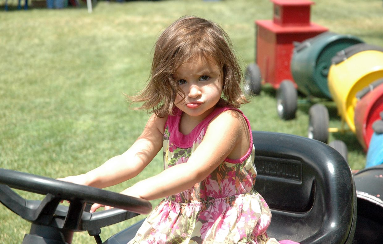 Two-year-old Tula Bringuel pretends to drive the tractor train at Saturday's annual Taste of South Routt festival in Oak Creek.