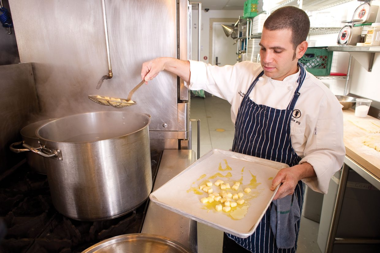 Chef Ezra Duker pulls potato gnocchi from a pot of boiling water while preparing a dish for the Truffle Pig restaurant.