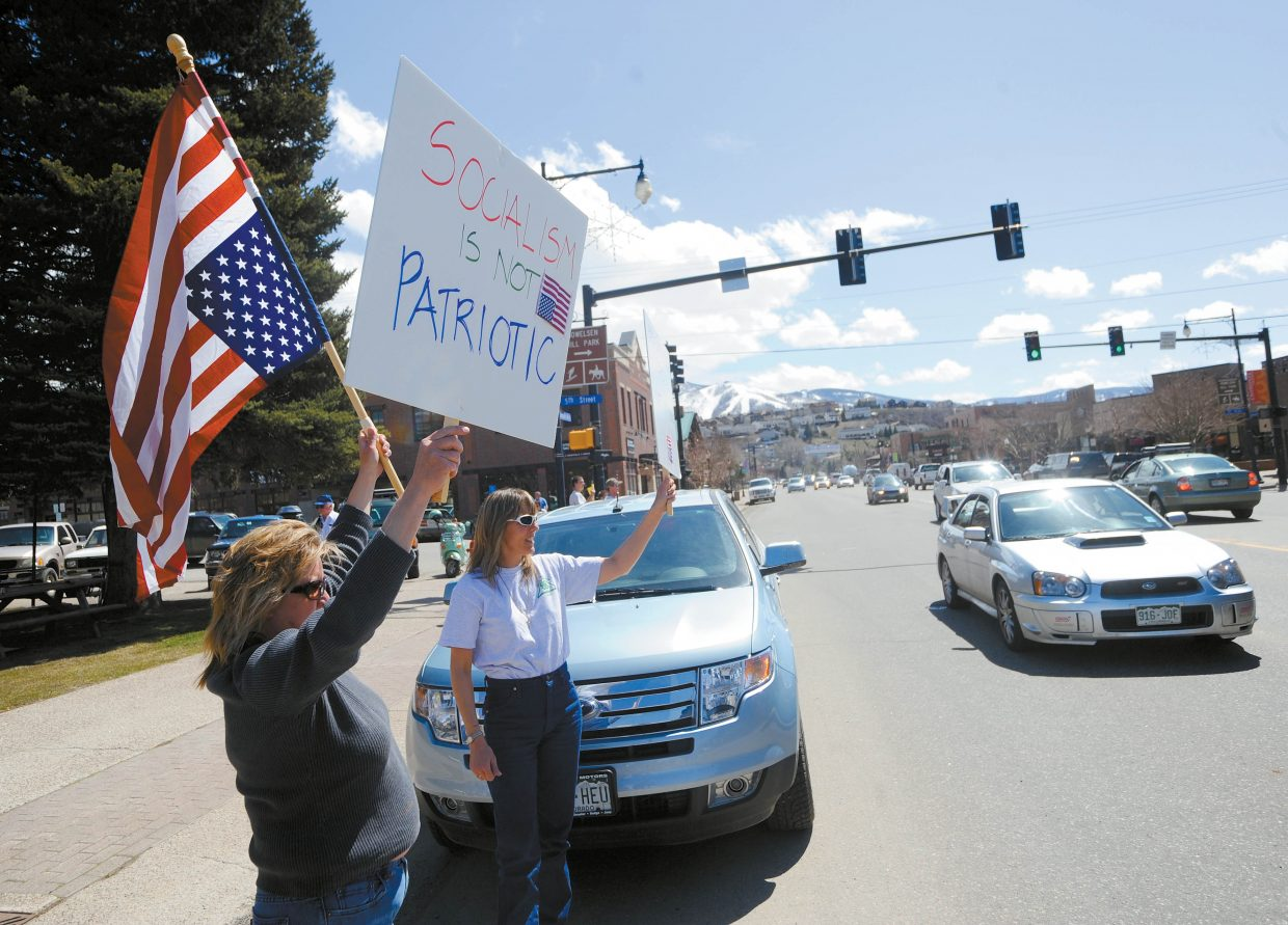 Steamboat Springs residents, from left, Leslie Weisshaar and Kirsten La Sovage hold signs along Lincoln Avenue during the Taxpayer Tea Party.