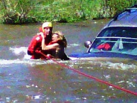 Oak Creek Fire Protection District Capt. Jeff Buffetti helps rescue Elizabeth Christensen on Wednesday after she crashed her car into the Yampa River.