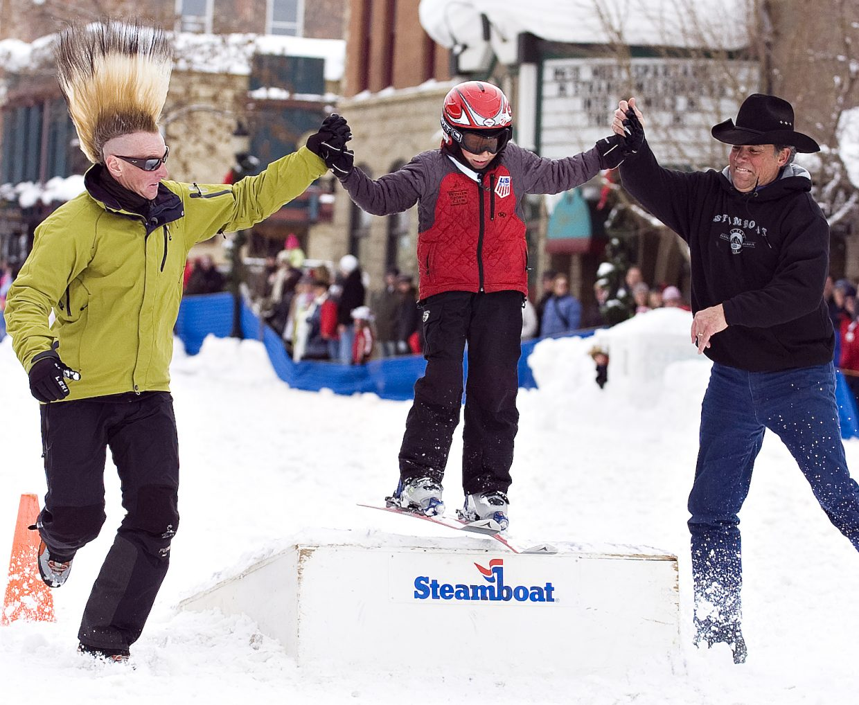 Skiing icon Glen Plake, left, and Scott Flower, right, help Cole Puckett jump the ramp on Lincoln Avenue during the Winter Carnival on Saturday.