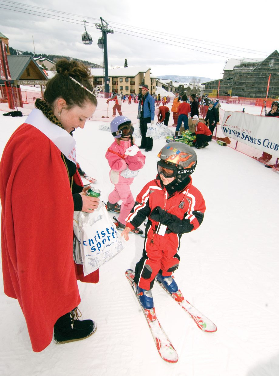"""Ski racer Brodie Pearson, 4, gets a """"Goody bag"""" from Winter Carnival attendent Erika Walters at the 2009 Soda Pop Slalom Friday at Steamboat Ski Area."""