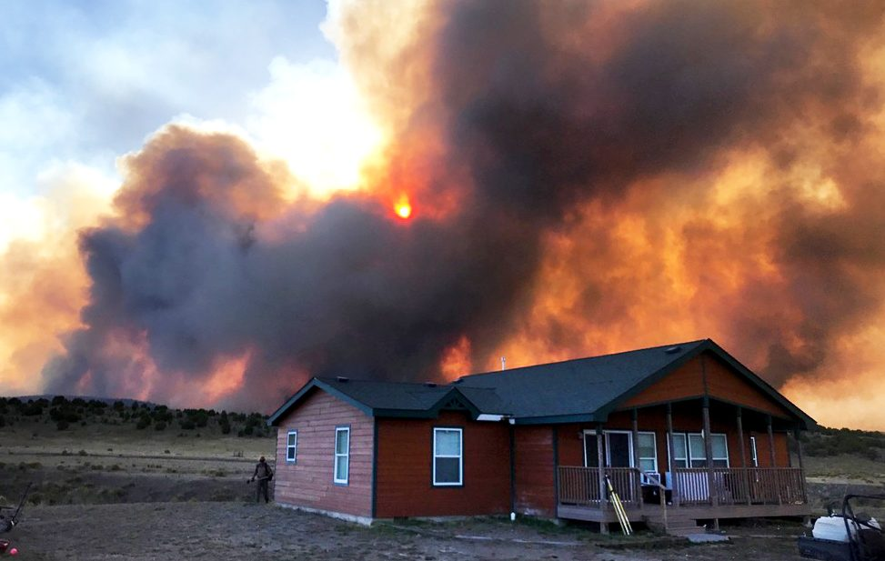 Smoke and flames from the Winter Valley Fire billow behind a residence Thursday afternoon as the fire whipped through Deerlodge Park in western Moffat County. The fire was first reported around noon Thursday and burned more than 3,500 acres by about 6:20 p.m.