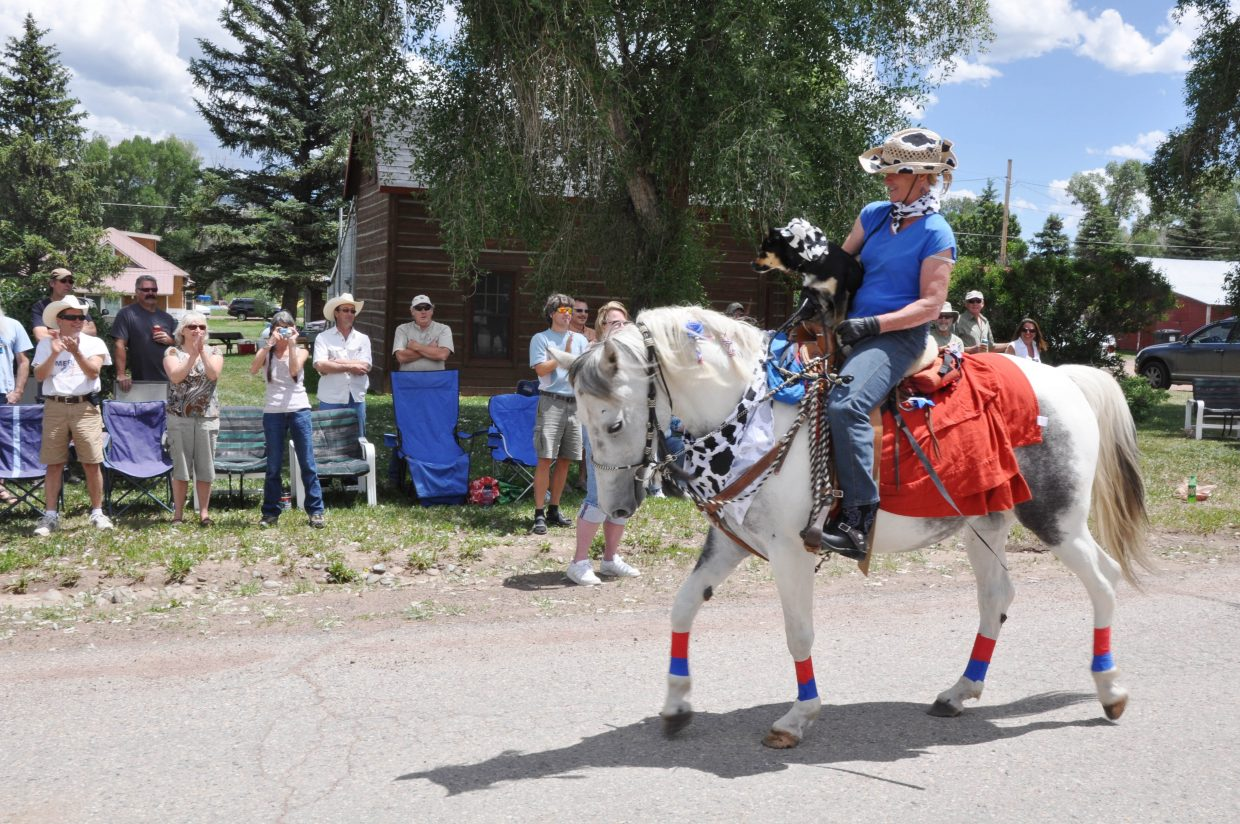 Jill Andrews rides her horse down Main Street in Yampa on Sunday as spectators cheer her on at the Yampa Fourth of July parade. Hundreds of spectators lined Yampa's streets to watch the parade.