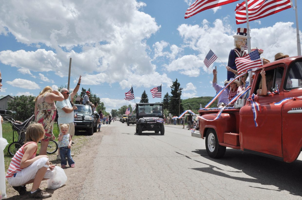 Spectators on Main Street in Yampa wave as cars pass by during the Fourth of July parade Sunday. The parade followed a pancake breakfast and was the highlight of a full day of holiday celebrations in Yampa.