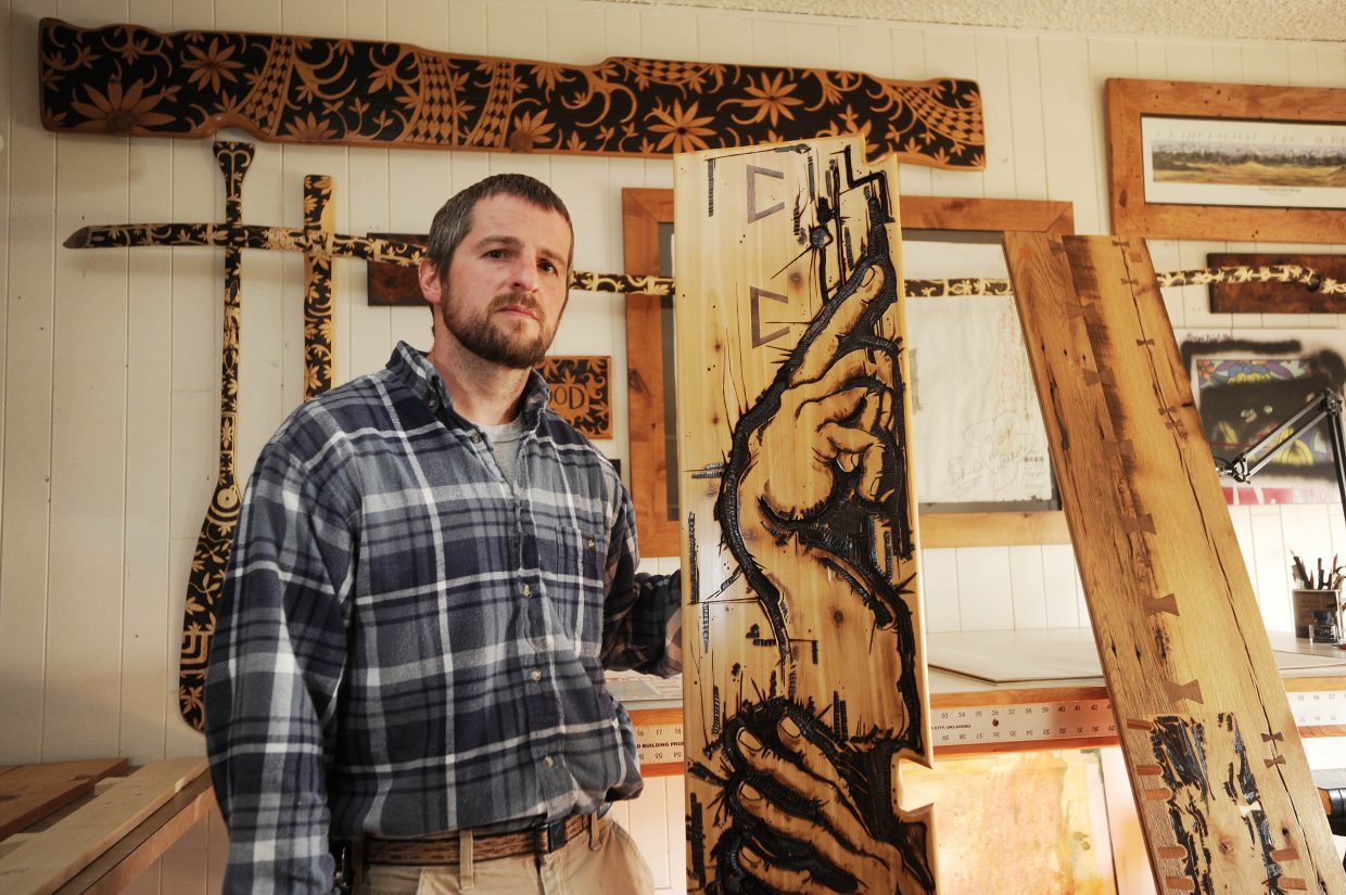 Steamboat Springs artist and carpenter Brian Leach stands with several of his wood-burned pieces.