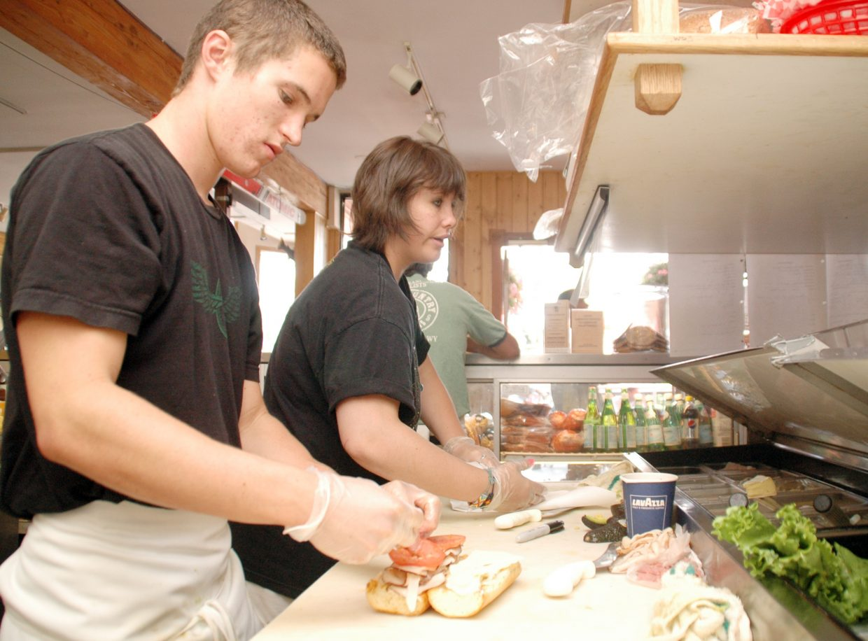 Taylor Coe, left, and Jamie Waugh build sandwiches at Backcountry Provisions in downtown Steamboat Springs. Store owner Peter Boniface said the downturn in the economy has led to fewer available jobs, which has in turn helped him keep the same staff together for more than a year, far longer than he was able to when jobs were plentiful in the area.