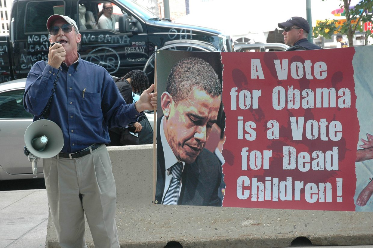 A demonstrator rails against Barack Obama's stance on abortion Monday, taking advantage of a crowded scene outside the Colorado Convention Center, where vendors sold Obama merchandise including T-shirts, buttons and car magnets. Other demonstrators voiced opinions about topics including meat production and health care.