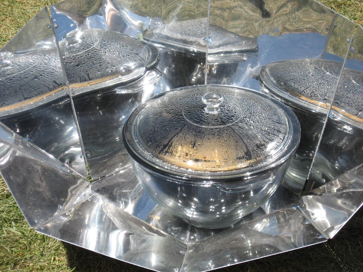 """Rice and beans cooks in a """"solar oven"""" displayed by the Colorado Renewable Energy Society on Tuesday, as the summer sun cooked all of Denver during the Democratic National Convention. Jennifer Beach of the CRES said solar ovens can be made at home by lining a wooden box with unrolled soda cans."""