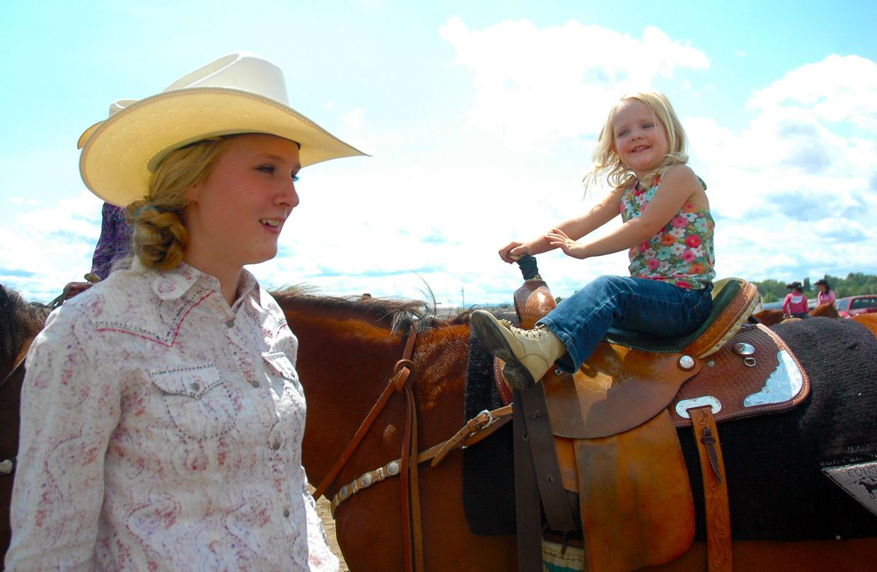 Teagann Yeager, 15, of Clark, lets her younger sister Oaklee, 2, sit on her horse as she waits for her event during Saturday's horse show at the Routt County Fair.