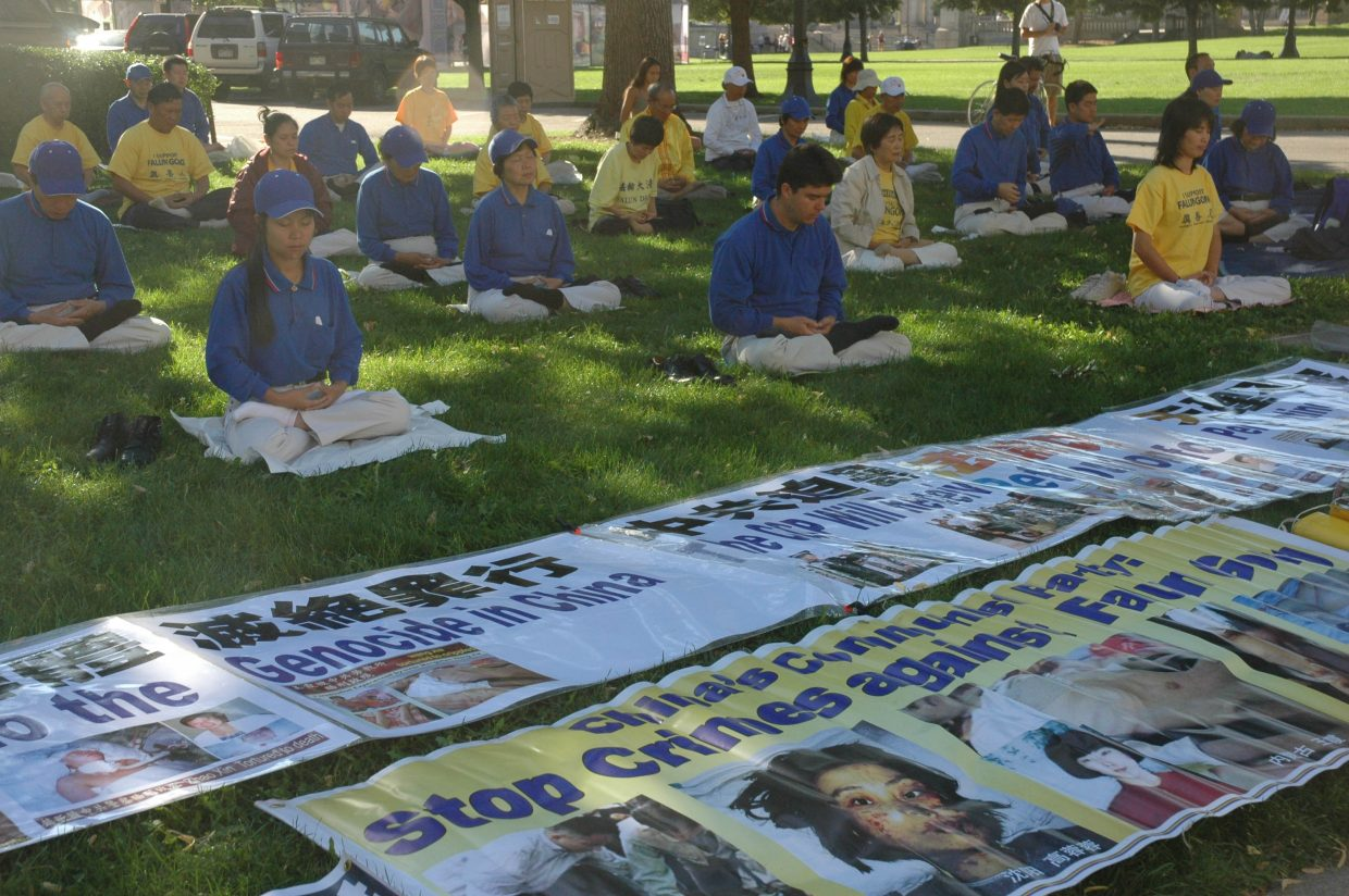 Supporters of the Chinese Falun Dafa spiritual practice meditate Monday morning in Denver's Civic Center Park, to raise awareness about human rights violations in China. Shortly after 8:30 a.m. Monday, the group was the first to make an organized appearance in the park, expected to be a hub for protest groups and events this week.