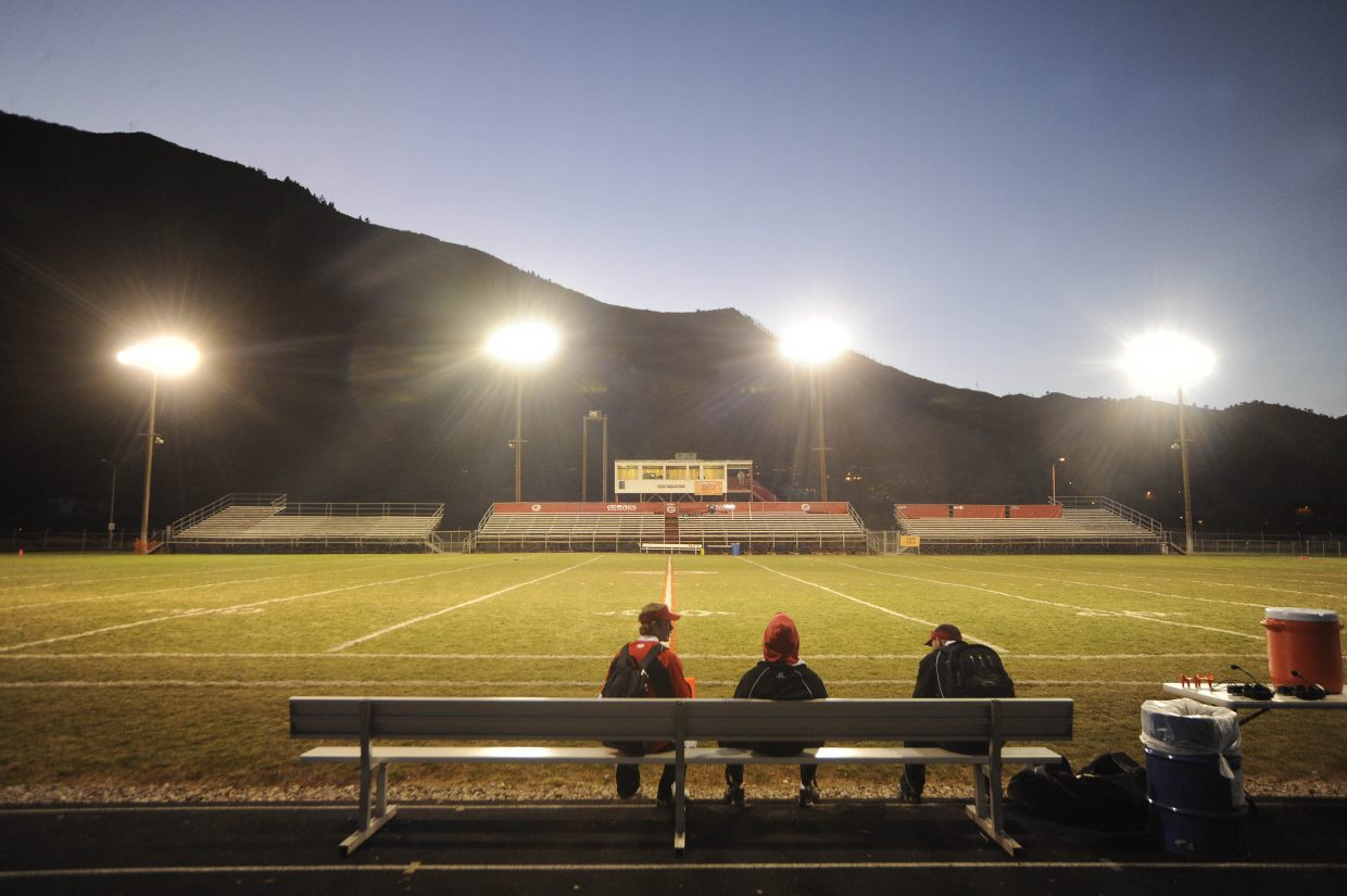 Steamboat Springs High School football coaches sit on the bench alongside the field Friday night at Glenwood Springs High School.