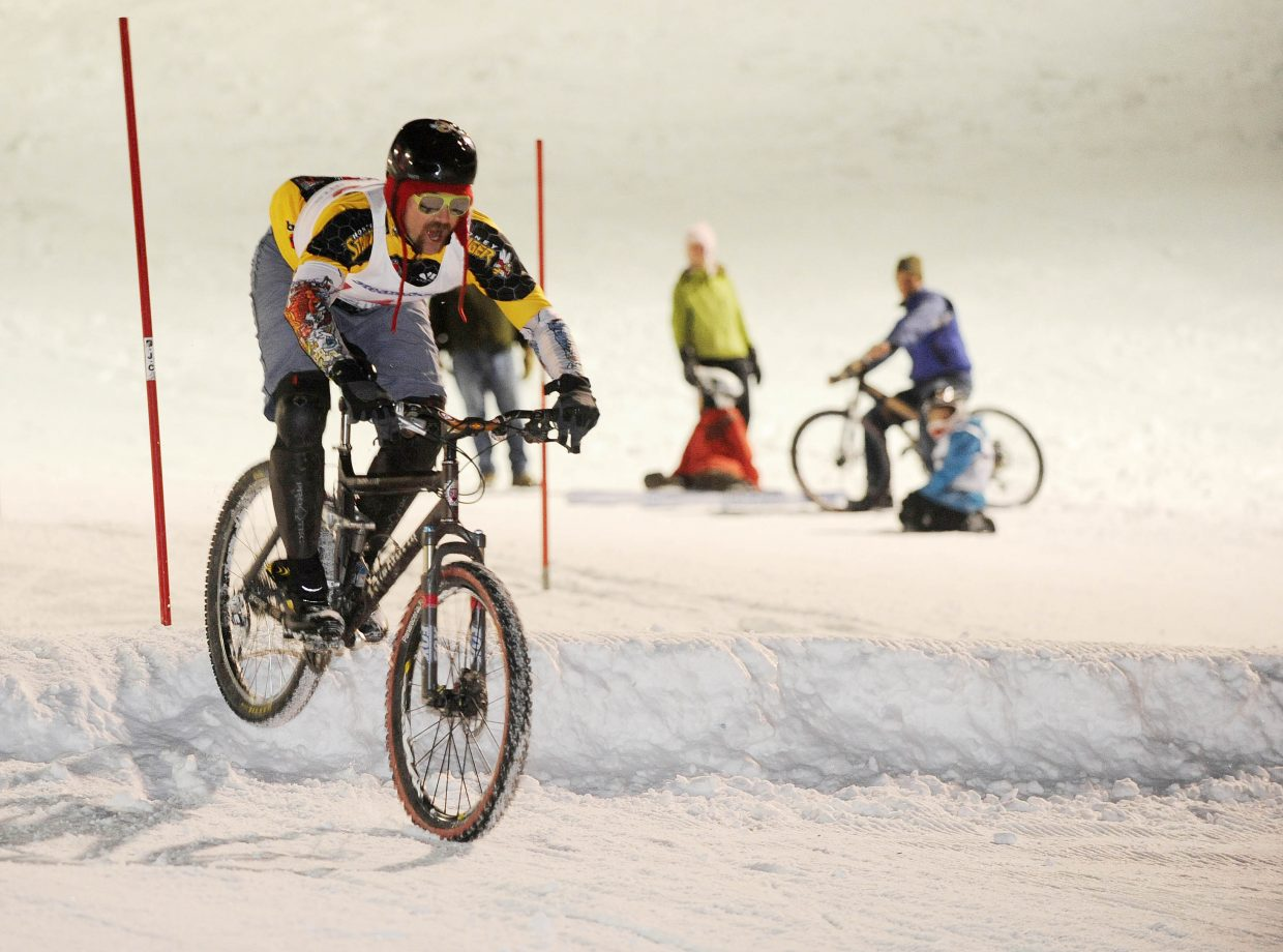 Steamboat Springs resident Rob Peterson hits the jump during the Wheels Bicycle Shop Dual Slalom Bicycle Race sponsored by Yeti Cycles on Friday night at Howelsen Hill.