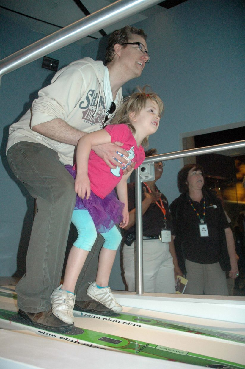 Denver resident Tyson Neidig and his daughter, Kira, 5, try the ski jump simulator Saturday at the History Colorado Center.