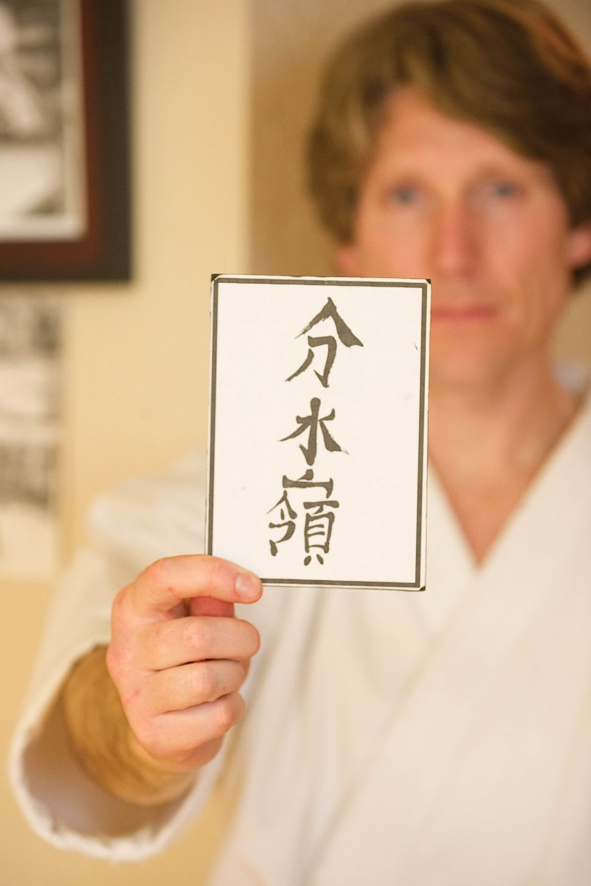 Michael David Bauk holds a card given to him by his own Sensei with the name of the karate studio in Japanese.