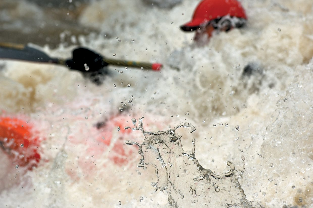 Water splashes off a rock and into the air as kayaker Joe Carberry plays in the rolling waters of the Yampa River last week.