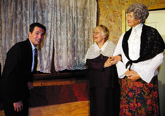 Mortimer Brewster (Matthew Stoddard) reacts after finding a body in the window seat as Abby Brewster (Rusty DeLucia) and Martha (Kay Wagner) look on, unphased by the discovery.
