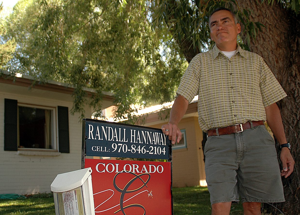 Rick Lobato stands with the real estate sign in front of his downtown Steamboat Springs home. Lobato moved to Steamboat in 2006 and started Chaparral Construction. Three years later, he said business has dried up. He's trying to sell his home and for the first time in his life, he's relying on unemployment pay.