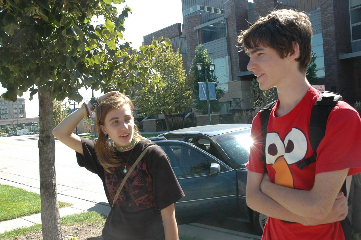 """Willie Theaker, 17, at right, and Lucy Piccochi, 23, drove to Denver from Connecticut for the DNC. Their car is behind them. The two slept Sunday night in """"The Freedom Cage,"""" the colloquial name given by convention attendees to the fenced free speech/protest area outside the Pepsi Center. Willie and Lucy said they plan to travel to Minnesota for the Republican National Convention next month, to voice their opinions about a government they do not support - and, they said, to take part in the fun, energetic convention atmosphere."""