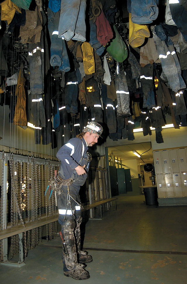 Miner Dan Kemry gets ready for his shift. Miners hang their clothing when they aren't working so it stays dry.