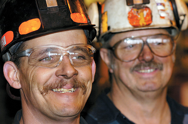 Shop mechanics Ty Reed, front, and Danny Green enjoy a laugh while working inside the maintenance shop at Twentymile Coal Co. While many of the employees at the mine work underground mining coal, others maintain machinery or hold above-ground jobs.