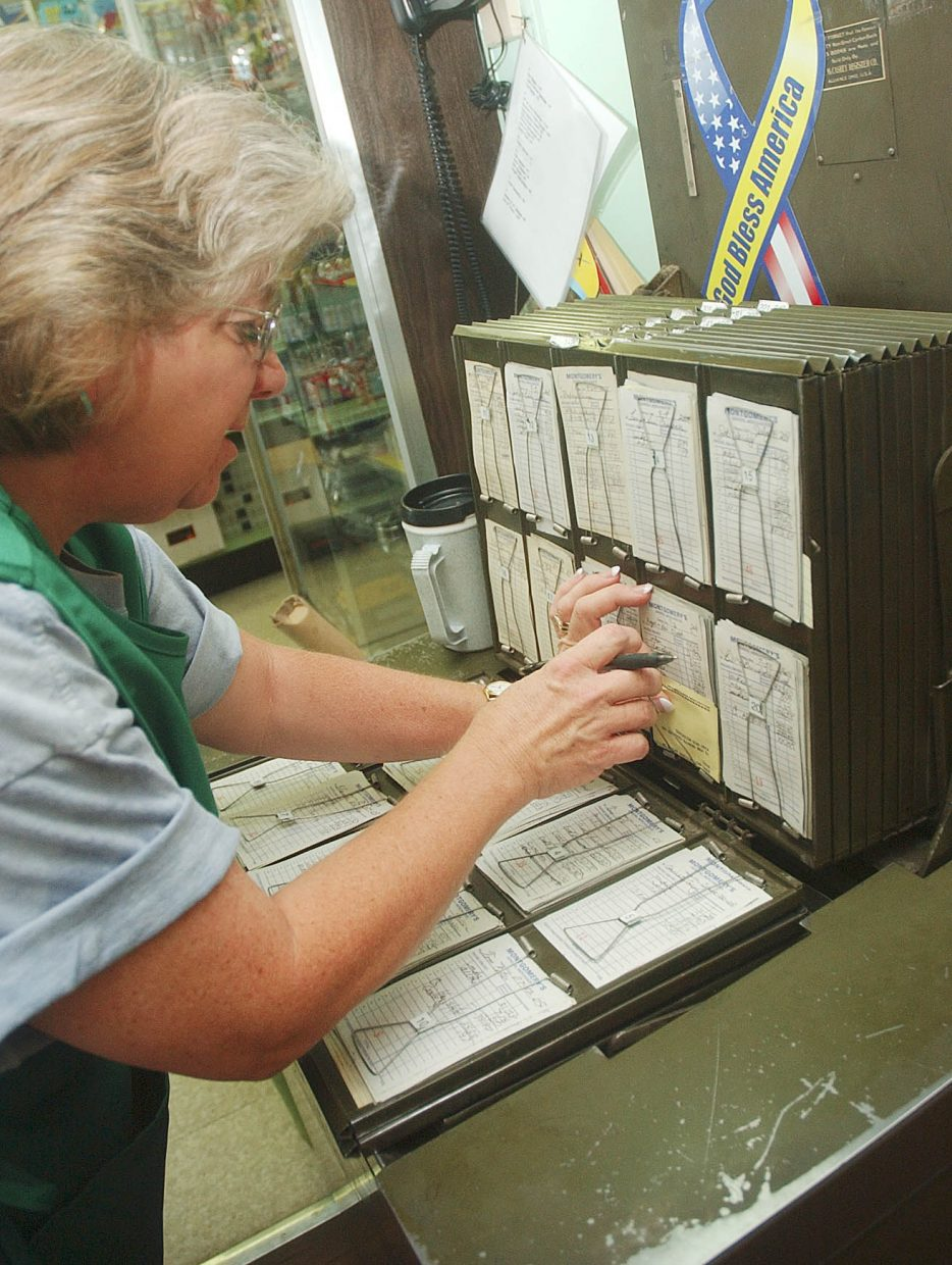 Cindia Montgomery looks for a customer's account Thursday at the store.