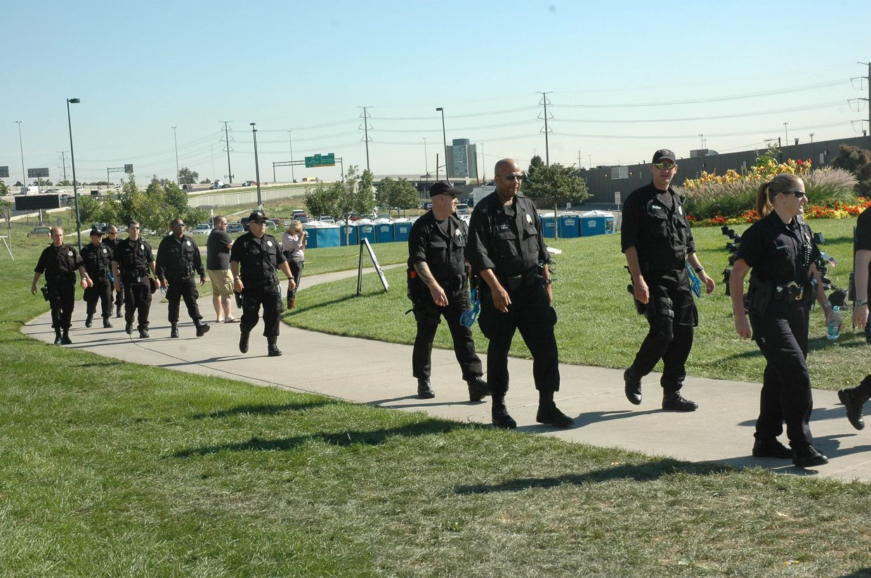 Police officers walk en masse through City of Cuernavaca Park in Denver on Monday morning. Law enforcement is making its presence felt already this week, patrolling in large groups - on foot, on horseback, on bikes, and in the occasional Humvee - throughout downtown and in areas that are expected to host protests.  An officer in this group declined an interview.