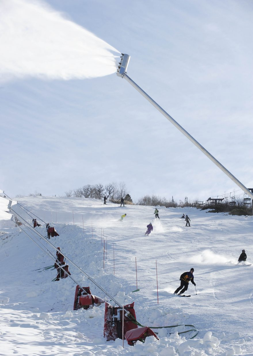 Skiers and snowboarders ride down the See Ya trail alongside snowmaking taking place on See Me.