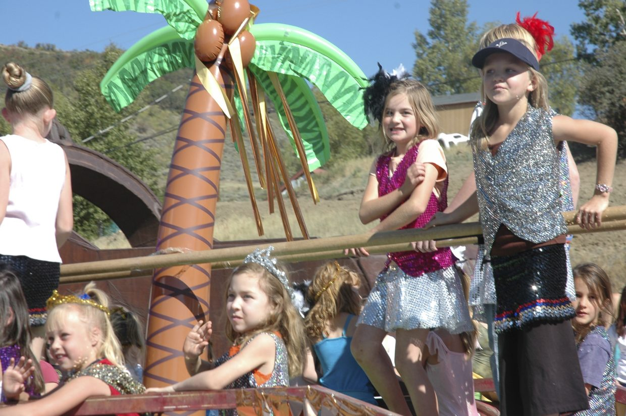 Girls from Let's Dance studio wave from their float during Oak Creek's Labor Day parade Monday.