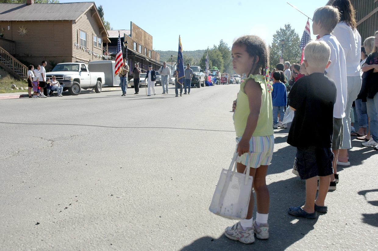 Children wait with candy bags ready as the first floats approach during Oak Creek's Labor Day parade Monday.