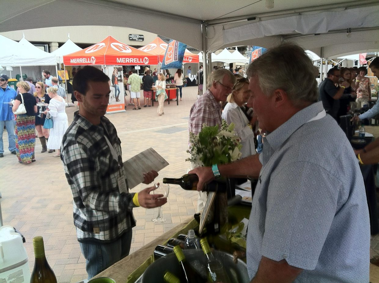 Rodney Schatz from the Peltier Station winery pours Tom Casazza a glass of wine Saturday at the Steamboat Wine Festival.