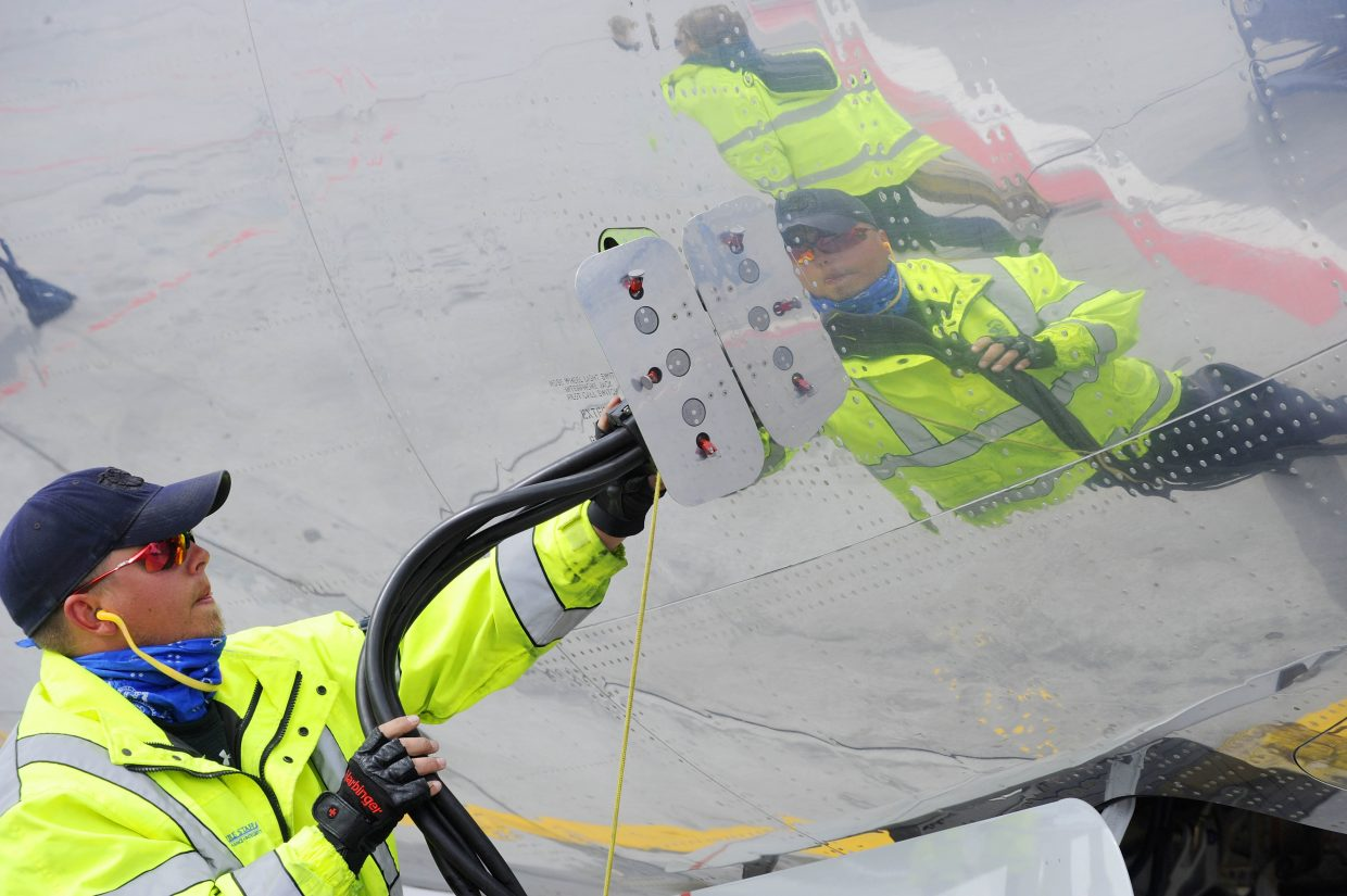Erik Plate hooks up an American Airlines 737 to auxiliary power Friday at Yampa Valley Regional Airport.