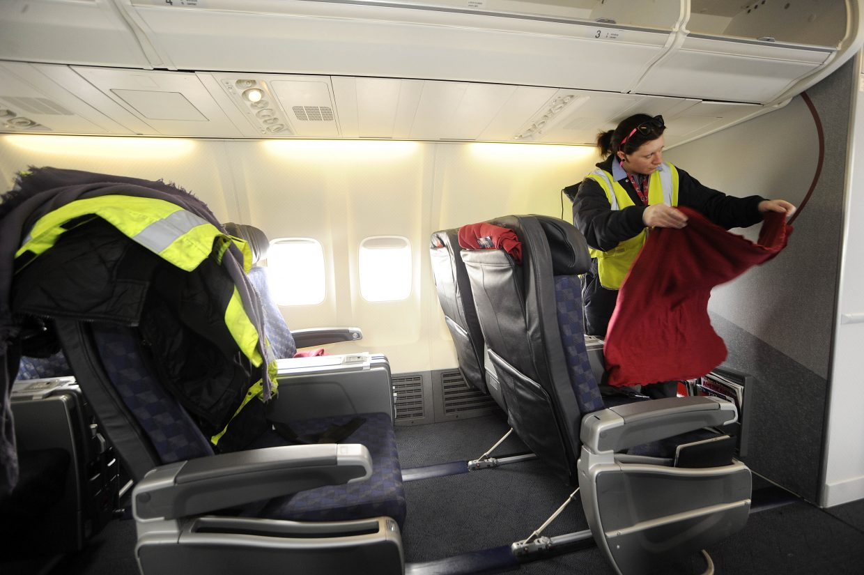 Maddy Attolini folds a blanket in the first class cabin of a American Airlines 737 that just arrived from Chicago.