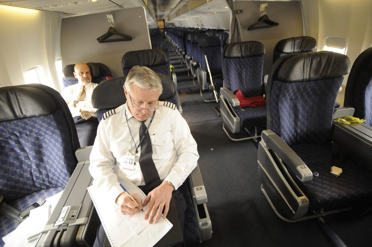 American Airlines Capt. Timothy Richard, front, and flight attendant Paul Holmes wait for their 737 to be prepared for another flight Friday.