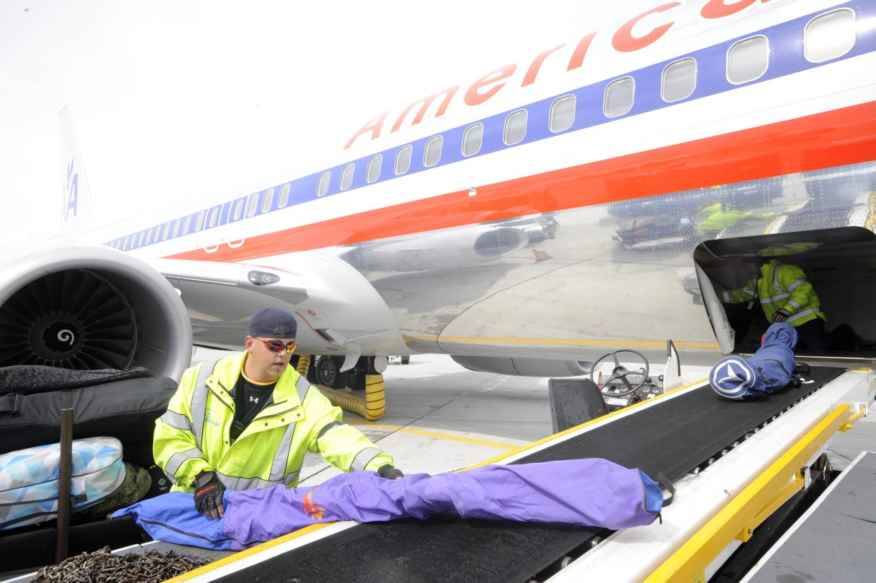 Erik Plate unloads skis from a American Airlines 737 that just arrived from Chicago on Friday.