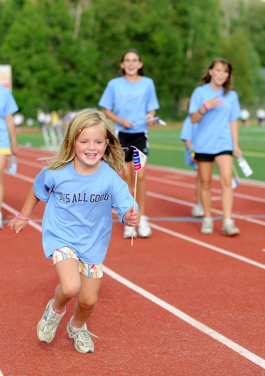 Five-year-old Ellery Hodges runs the track wearing a shirt showing her support for Jason Sear, who recently died after an 18-month battle against cancer.