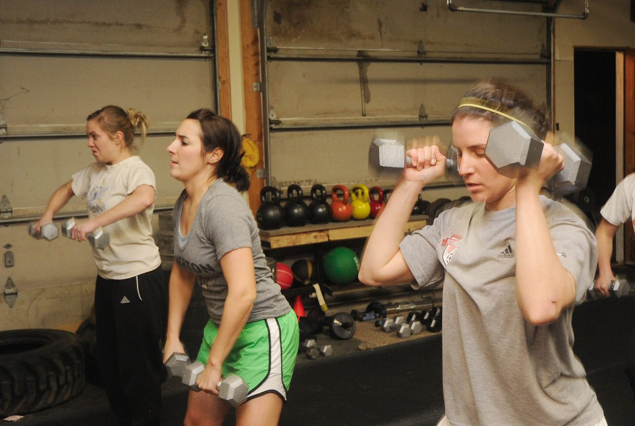 Julie Wernig, right, Tara Wernig, middle, and Laura Philip work with dumbbells.