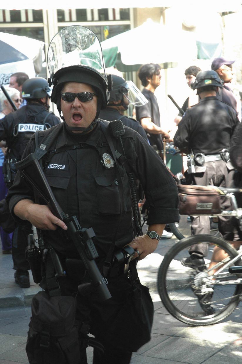 A police officer on the 16th Street Mall orders people onto the sidewalks Monday in downtown Denver.