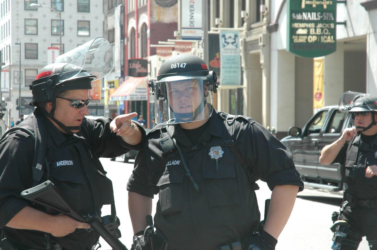 Two police officers discuss a contentious crowd developing on the 16th Street Mall on Monday afternoon. Law enforcement arrested several protesters Monday night in Civic Center Park, using pepper spray to disperse crowds.