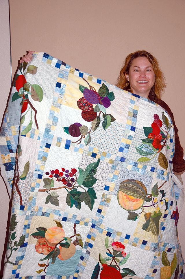 Tina Segler with her favorite quilt that she is sewing by hand and is all applique.