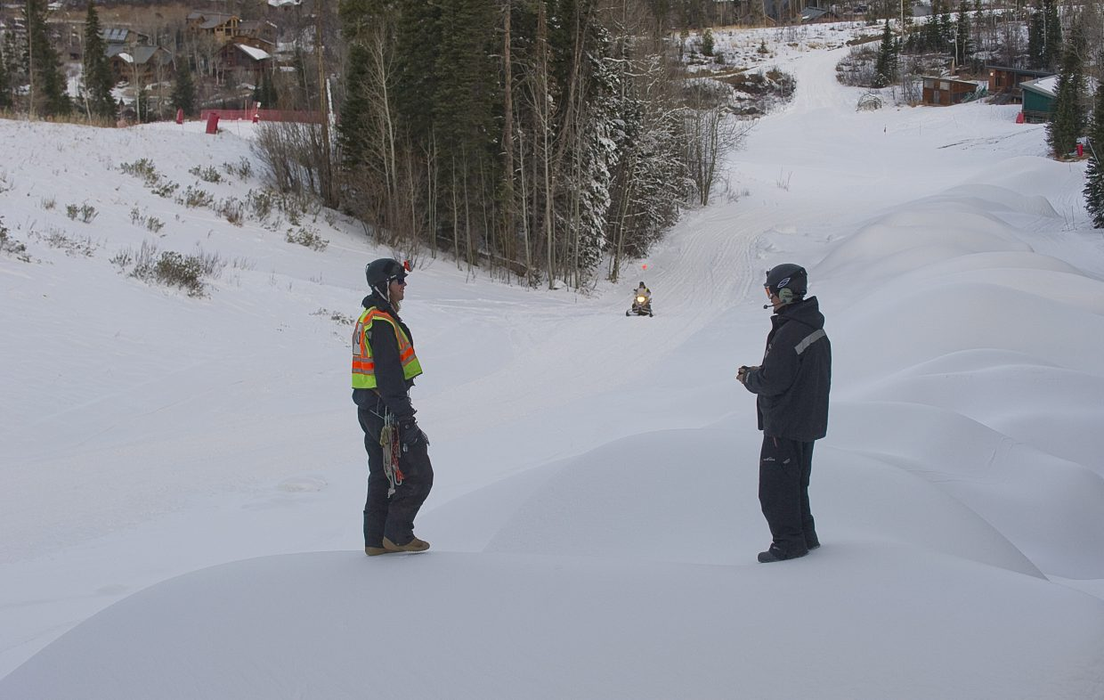 Snowmaking technician Pierce Delhaute visits with a co-worker on one of the large piles of snow made by snowmaking crews at Steamboat Ski Area.