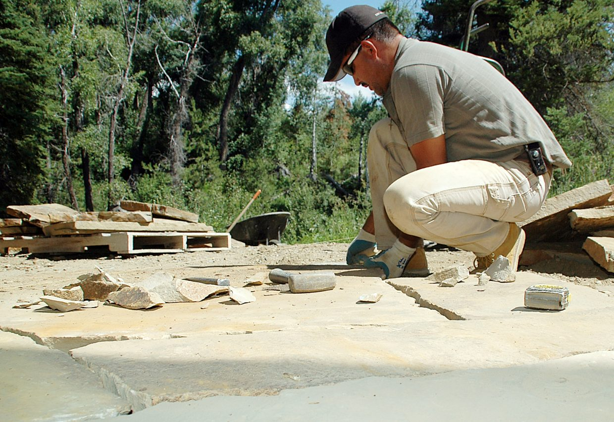 Lence Tirco works laying stone behind a Stonewood neighborhood house in Steamboat Springs.