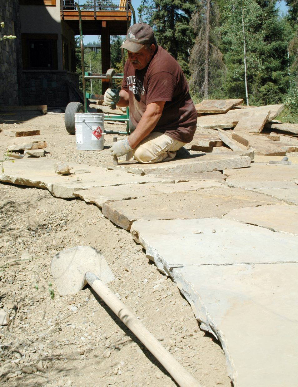 Narciso Silva Hernandez chisels on a stone down while building a limestone walkway behind a house in the Stonewood neighborhood in Steamboat Springs.