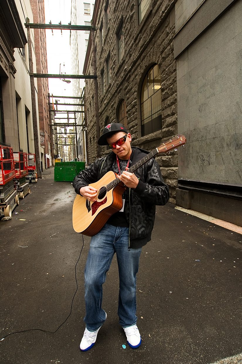 An alley serves as a backdrop for street performer Brian Merkl, who was performing as tourists and Olympic visitors walked down one of the crowded Vancouver streets near the International Broadcast and Main Media centers for the Olympic Games.