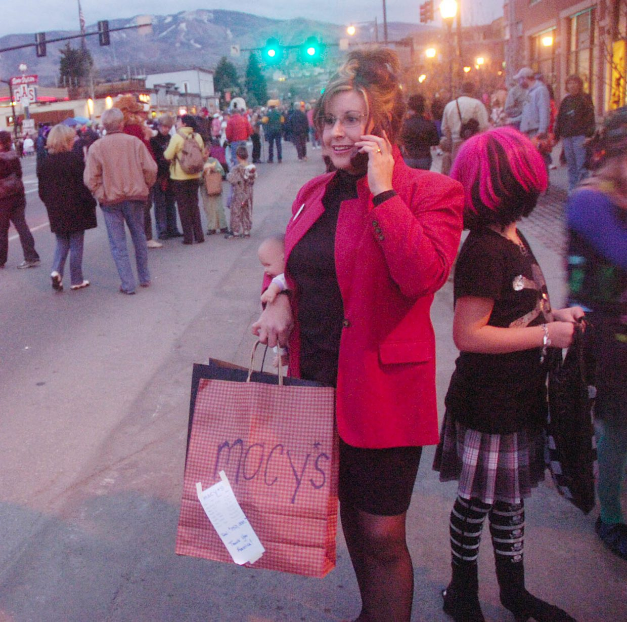 Stagecoach resident Jennifer Johnson, dressed as Sarah Palin, talks on her cell phone next to her 9-year-old daughter Emma on Friday night during the Downtown Halloween Stroll.