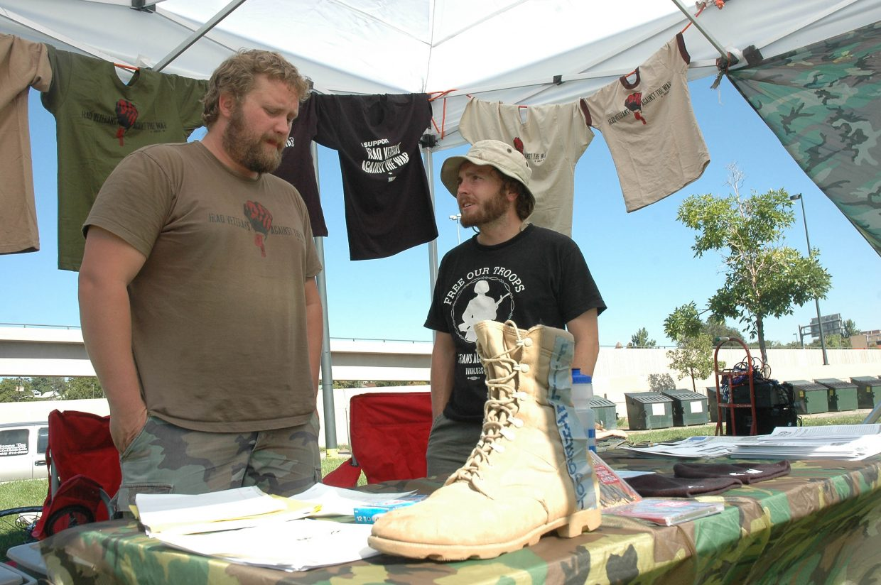 """Ben Schrader of Fort Collins, left, works with David Mann of Colorado Springs in an Iraq Veterans Against the War booth Monday morning in Denver's City of Cuernavaca Park. Schrader, 28, served in Iraq with the U.S. Army in 2004 and early 2005. He said the devastation he saw as a calvary scout in Baquba made him """"not believe in war."""" Iraq Veterans Against the War has chapters across the U.S. Tuesday, Schrader said, the group is planning to stage mock Iraq War scenarios - including taking prisoners and """"securing areas"""" - in downtown Denver."""
