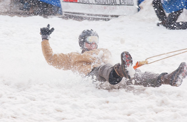 Adam Elmers rides down Lincoln Avenue on a shovel pulled by a galloping horse during the Shovel Race.