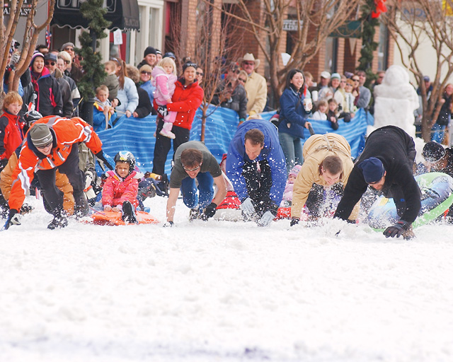 Dads kick up snow as they pull their kids during the 25-yard Dog and Dad Dash. For more photos, see page 12A or visit www.steamboatpilot.com.
