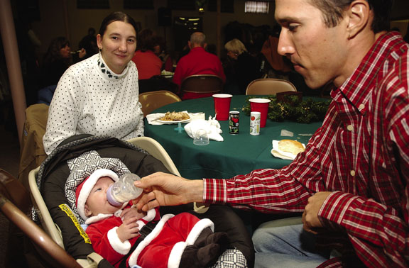 Daniel Rodgers feeds his 2 1/2-month-old son, Zachary, formula during the Steamboat Springs Board of Realtors Community Christmas Dinner. Also pictured is Zachary's mother, Alicia McKelvey.